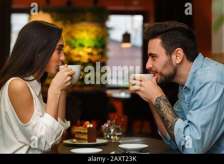 Couple Having Coffee Sitting In Cozy Cafe, Side View - Stock Photo
