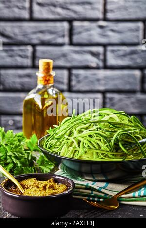 spiralized Zucchini spaghetti, zoodles in a black bowl on a grey concrete table with sauce pesto and ingredients with a brick wall at the background,