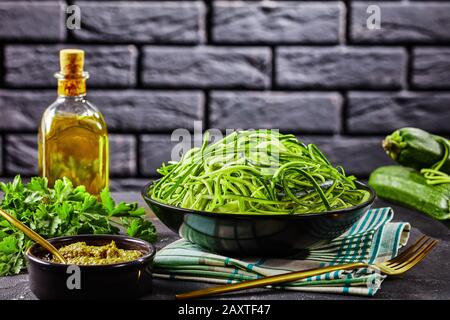 spiralized Zucchini spaghetti, zoodles in a black bowl on a grey concrete table with sauce pesto and ingredients with a brick wall at the background, - Stock Photo