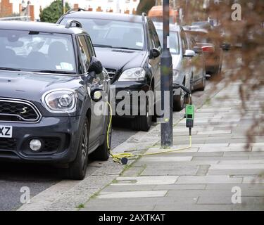 Mini Metro electric car being charged from a lamp post on a street in London - Stock Photo