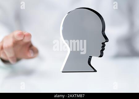 A person touching a virtual projection of a human head - frame of mind concept - Stock Photo