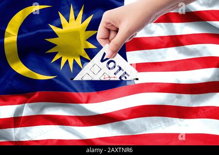 Malaysia general election concept. close up hand of a person casting a ballot at elections during voting on canvas Malaysia flag background. - Stock Photo