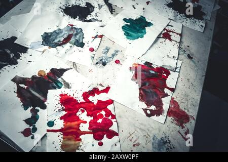 Many red colored blots on white paper with streaks. Abstract creative spots of paint on a white background. Red bright colors. Stained-spattered table - Stock Photo