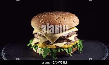 Closeup of king size cheeseburger isolated on black background - Stock Photo