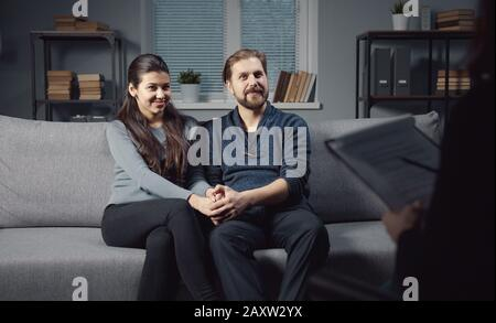 Happy spouses sitting on sofa holding hands at psychology session - Stock Photo