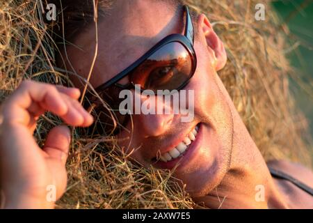 A portrait of a beautiful man in a haystack. - Stock Photo