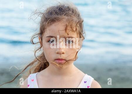 Portrait of cute sad little girl, standing at the seaside
