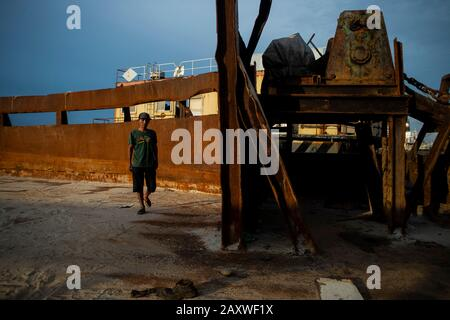 (200213) -- JAKARTA, Feb. 13, 2020 (Xinhua) -- A worker walks on an old ship before it is cut to recycle at a ship breaking yard in Cilincing, Jakarta, Indonesia, Feb. 13, 2020. Ship breaking is a recycling process in which vessels are taken apart and sold as scrap metal. (Xinhua/Agung Kuncahya B.) - Stock Photo