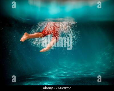 Underwater picture of a boy swimming in a pool - Stock Photo