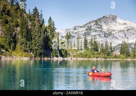 Retired woman enjoying a paddle on remote mountain lake.