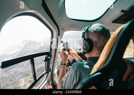 Retired man takes photo with phone from inside helicopter. - Stock Photo