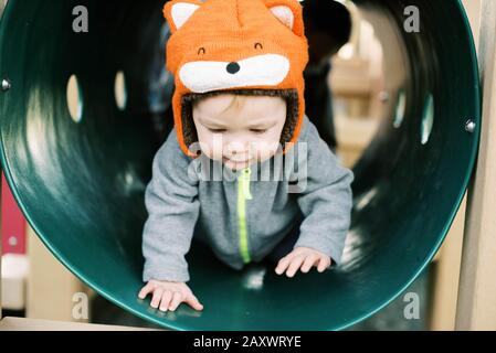 Little boy with fox hat playing at the playground.