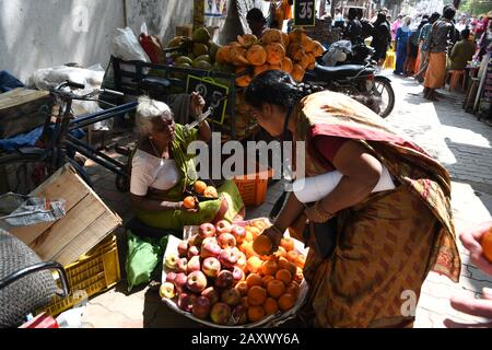 An old Indian lady selling oranges on a busy street in Madurai, Tamil Nadu, India - Stock Photo