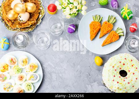 Funny colorful Easter food for kids with decorations on table. Easter dinner concept, top view - Stock Photo