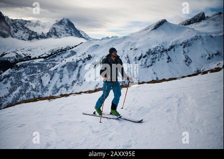 A ski mountaineer climbing a mountain using his skis. Switzerland. - Stock Photo