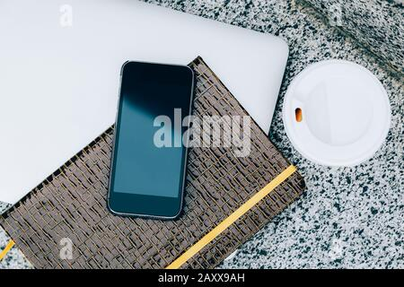 Office working desk top view with laptop, smartphone, notepad and coffee cup - Stock Photo