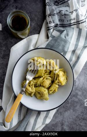 Cooked tortellini on a plate, close up pasta, italian food. Dark background. - Stock Photo
