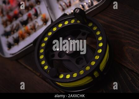 Fly Fishing reel and box of flies - Stock Photo