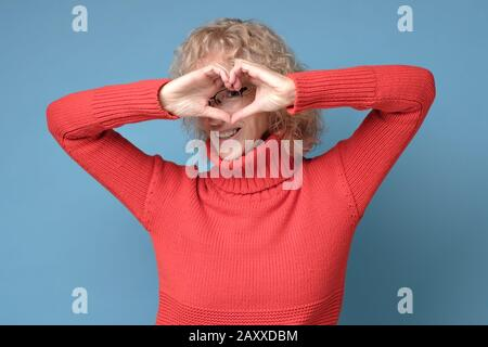 Smiling cheerful happy senior woman making heart sign with hands isolated on blue wall background. Positive human emotion expression feeling life perc - Stock Photo