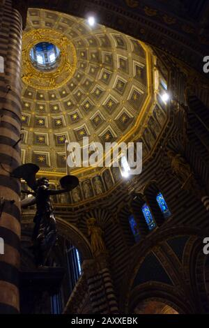 View from below the inner dome of the Cathedral of Siena. Dome decorated with stars with next to it a statue of a black angel holding the candle. - Stock Photo