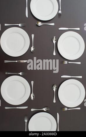 Dark table set for six people with clean white plates and cutlery viewed from above - Stock Photo