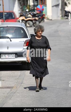 Old greek widow walks in the street of a village - Stock Photo