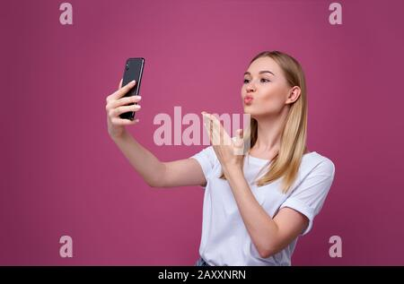 Portrait of a young attractive woman making selfie photo on smartphone isolated. Blonde woman - Stock Photo