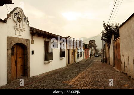 Picturesque street view with cobblestone streets and Spanish colonial buildings during sunset. Antigua, Guatemala. Jan 2019