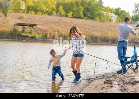 Mom with a small son walks along the sandy shore of the lake in rubber boots. Hanging out with children in nature, away from the city. - Stock Photo