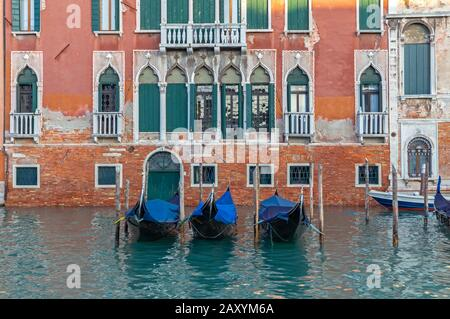 Parked gondolas on Grand Canal in Venice at high tide - Stock Photo