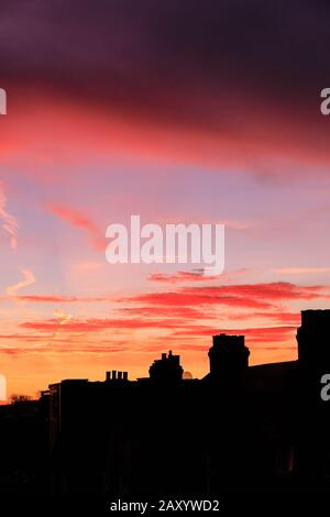 London, UK. 14th Feb, 2020. A beautiful red and orange sunrise with colourful cloud formations appears over the roof tops of South East London, just in time for Valentine's Day 2020. Credit: Imageplotter/Alamy Live News - Stock Photo