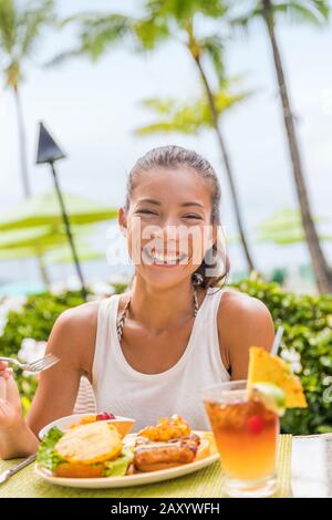 Happy woman at restaurant eating Hawaii burger with pineapple and karaage fried chicken. Hawaiian japanese fusion food. Asian girl at hotel restaurant table during summer travel vacation. Stock Photo