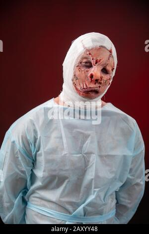 Crazy zombie horror make up. Person in blue madical shirt and bandaged head. Scars, deep scratches realistic art make-up. head is re-banded bandage - Stock Photo