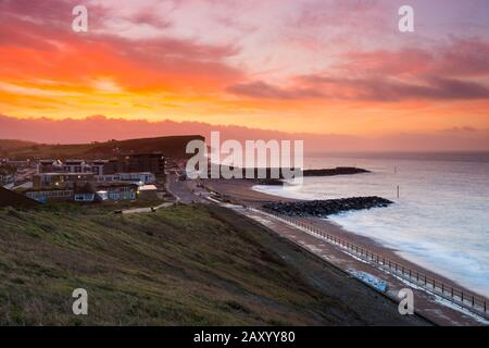 West Bay, Dorset, UK.  14th February 2020. UK Weather.  A red sky at dawn on valentines day shortly before sunrise at West Bay in Dorset ahead of the forecast bad weather from Storm Dennis.  Picture Credit: Graham Hunt/Alamy Live News