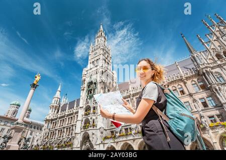 Happy asian woman with map searching for sights and interesting places in Munich city with Town Hall at the background.