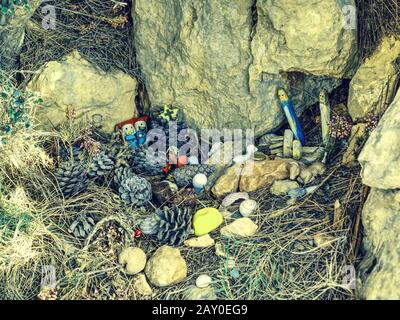 Kids create nativity from plastic figures and natural materials. Hikers go around put there small presents. - Stock Photo