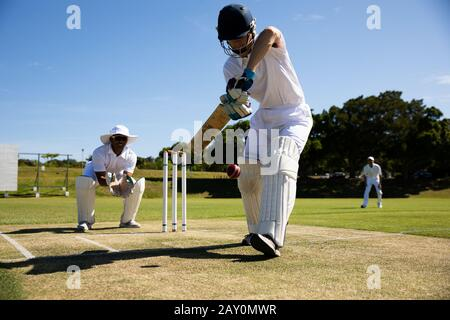 Cricket player shooting in the ball - Stock Photo
