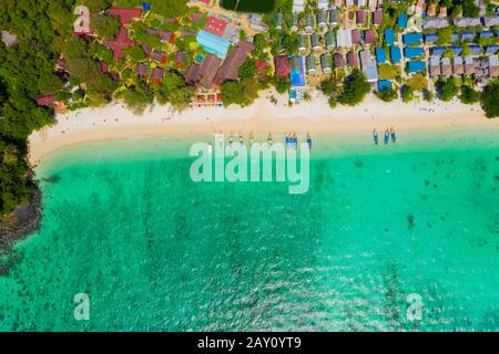 View from above, stunning aerial view of a beautiful tropical beach with white sand and turquoise clear water, long-tail boat and people sunbathing,Lo - Stock Photo