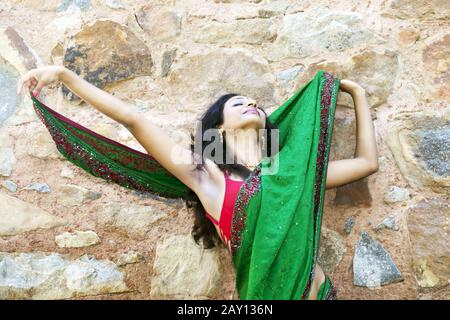 Indian woman in a saree on a stone wall