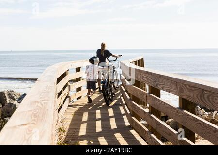 Two children, brother and sister on wooden bridge with bikes - Stock Photo