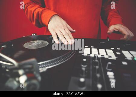 Hip hop dj scratches vinyl records on turntable player.Professional disc jockey mixes music with sound mixer and turn tables in nightclub.Concert djs - Stock Photo