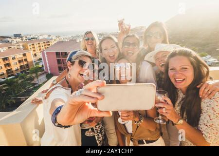 Group of happy and cheerful young women have fun in party together outdoor taking selfie picture with phone - people celebrate with wine and toasting - Stock Photo
