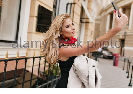Attractive blonde woman making selfie standing beside iron fence and gently smiling. Tanned girl in black dress taking photo of herself holding smartphone. - Stock Photo