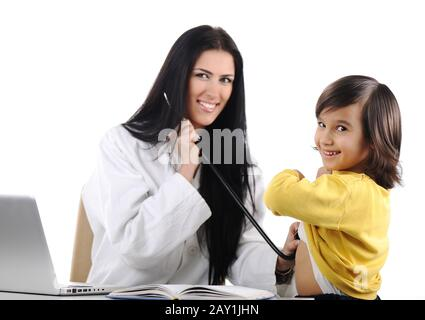 Young female doctor examining little cute child at modern hospital - Stock Photo