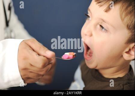 Doctor giving a child a spoon filled with pills - Stock Photo