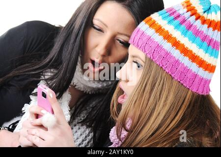 Two female friends reading sms message on cell phone - Stock Photo