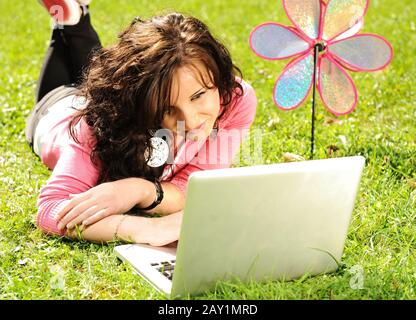 Happy young girl laying on green grass in nature and working on laptop - Stock Photo