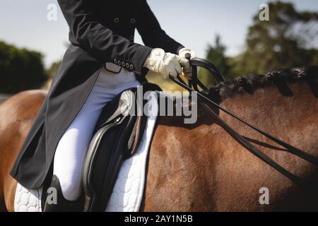 Caucasian woman riding her dressage horse - Stock Photo