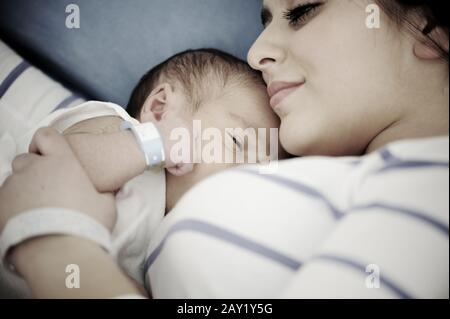 Woman holding her newborn baby at hospital - Stock Photo