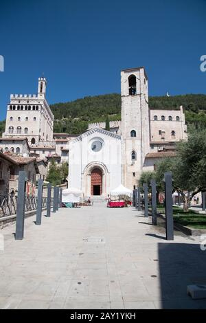 Romanesque Gothic Chiesa di San Giovanni Battista (St. John the Baptist church), filming location of Italian TV series Don Matteo, and Gothic Palazzo - Stock Photo